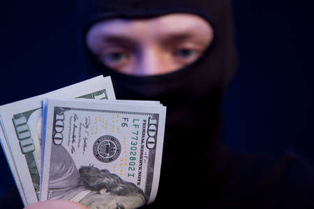 hijack: Thief. Man in black mask holding the money Stock Photo