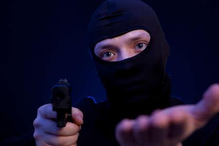 man holding gun: Man holding gun over dark blue background Stock Photo