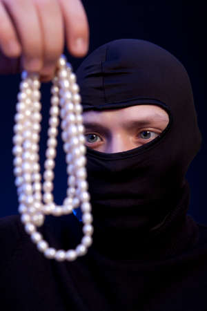 looting: Thief. Man in black mask with a pearl necklace over dark blue background Stock Photo