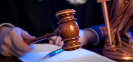 court judge: Judge. Male judge in a courtroom striking the gavel