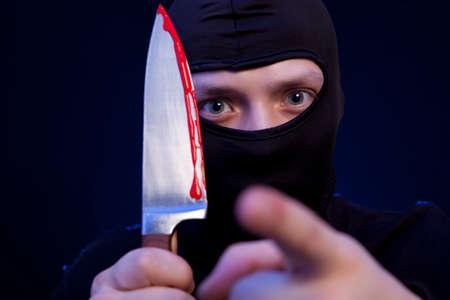 desperado: Man criminal in black mask with knife over dark blue background