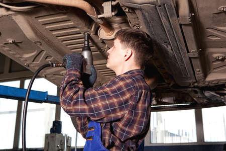 Worker of service station repairing car. Man repairing car