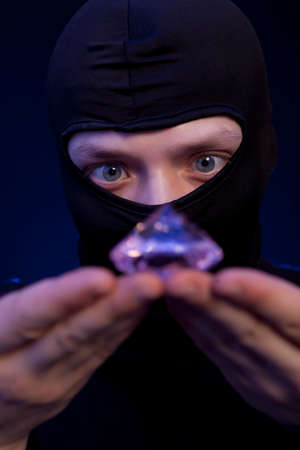 looting: Thief. Man in black mask with a big emerald over dark blue background Stock Photo