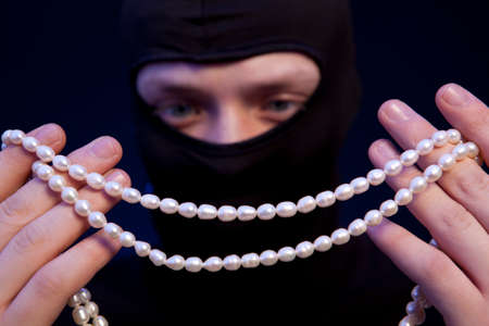 felon: Thief. Man in black mask with a pearl necklace over dark blue background Stock Photo
