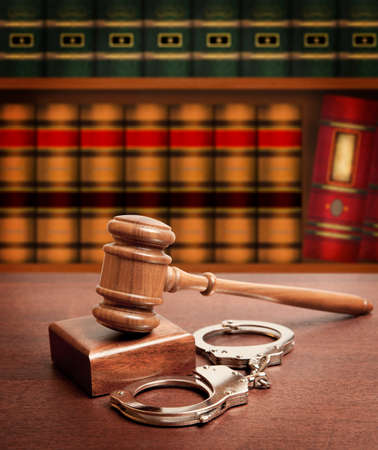criminal: Gavel and handcuffs on wooden background