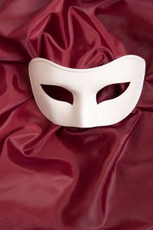 canvass: White theatrical mask and red silk fabric Stock Photo