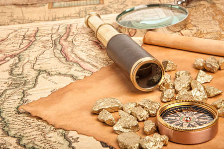 monocular: Gold nuggets and vintage brass telescope on antique map