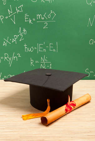rewarded: Gortarboard and graduation scroll, on the background of school board Stock Photo