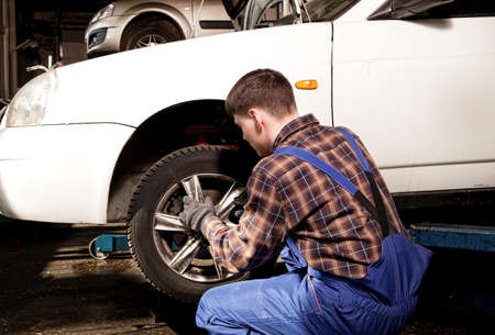 screwing: Car mechanic screwing or unscrewing car wheel of lifted automobile by pneumatic wrench at repair service station Stock Photo