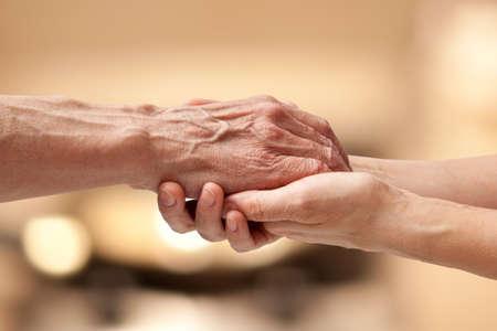 vecchiaia: Mani femminili toccando vecchia mano maschio - prendersi cura del concetto anziani