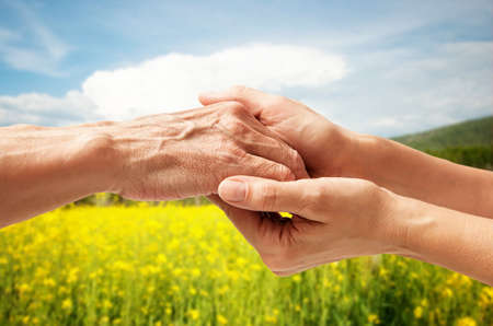 old hand: Autumn. Hands of an elderly senior holding the hand of a woman Stock Photo