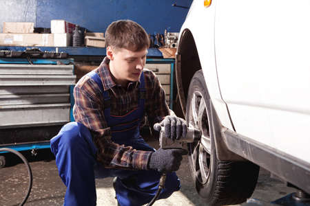 car service: Car mechanic screwing or unscrewing car wheel of lifted automobile by pneumatic wrench at repair service station Stock Photo