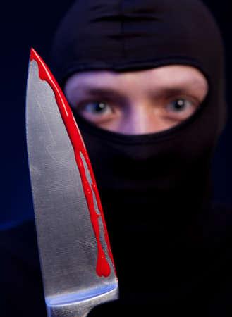 male killer: Man criminal in black mask with knife over dark blue background