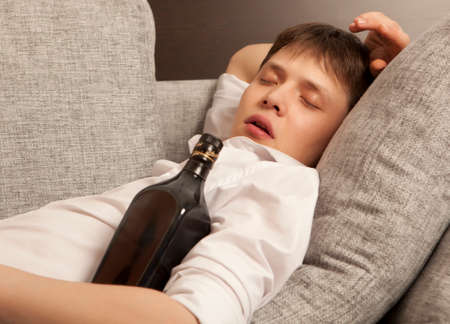 drinking problem: Drunkard. A young man with a drinking problem is relaxing on a sofa