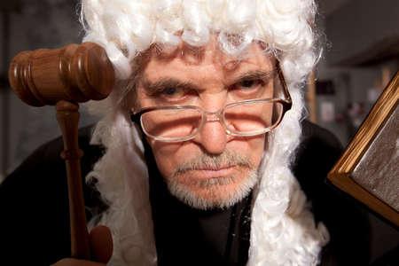 Rechter. Oude mannelijke rechter in een rechtszaal slaan van de hamer