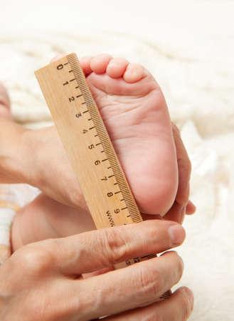 pie bebe: Conceptos de negocio de inicio. Pies recién nacidos del bebé en manos de la madre y regla Foto de archivo