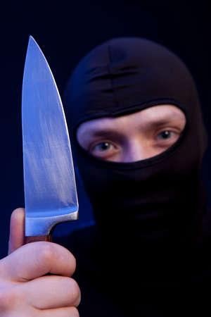 headgear: Man criminal in black mask with knife over dark blue background