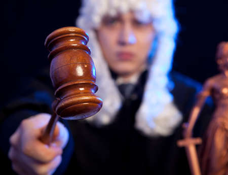 adjournment: Judge. Male judge in a courtroom striking the gavel