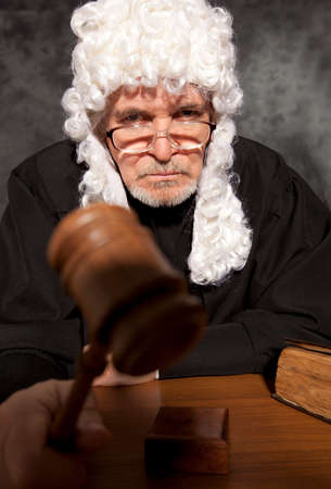 adjournment: Judge. Old male judge in a courtroom striking the gavel