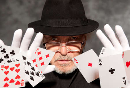 conjuror: Magician show with playing cards. On grey background