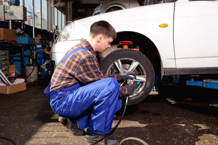 disassembly: Car mechanic screwing or unscrewing car wheel of lifted automobile by pneumatic wrench at repair service station Stock Photo