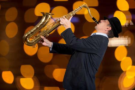improvisation: Saxophonist. Man playing on saxophone against the background of beautiful light