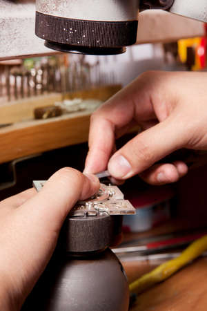 crafting: Jeweler crafting silver jewelry on his workbench