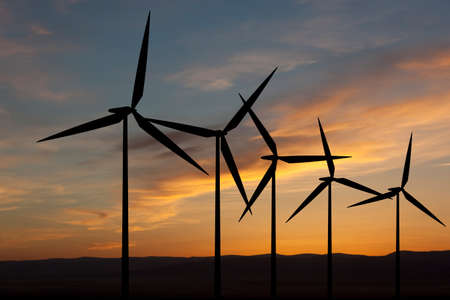 conservation: Wind turbine farm with rays of light at sunset Stock Photo