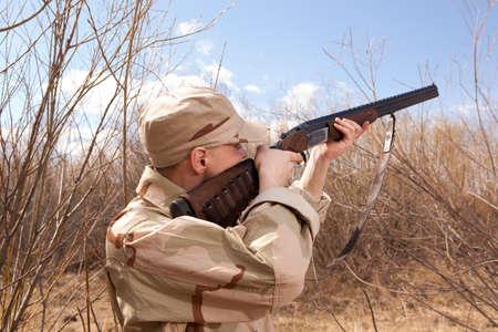 Hunter dans des vêtements de camouflage prêt à chasser avec fusil de chasse