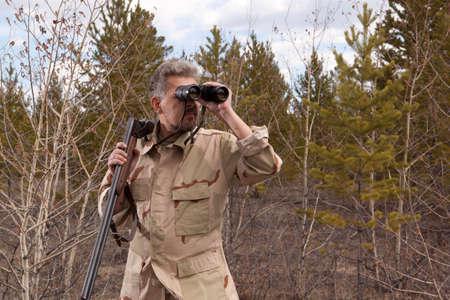 cazador: Cazador con escopeta mirando a través de binoculares en el bosque