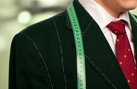 tailored: Tailor concept.  Businessman getting measured by a tailor