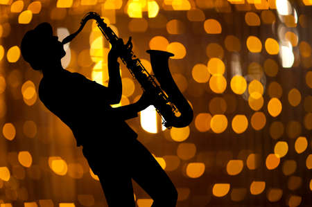 woodwind instrument: Saxophonist. Woman playing on saxophone against the background of beautiful light