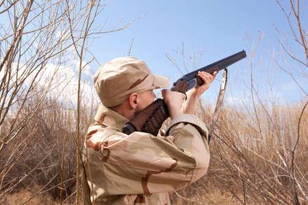 cazador: Hunter en ropa de camuflaje listos para cazar con escopeta de caza