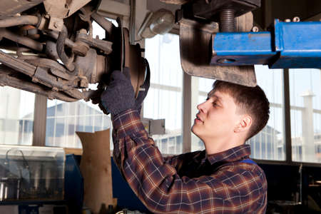 disassembly: Car mechanic inspecting car wheel and suspension detail of lifted automobile at repair service station Stock Photo