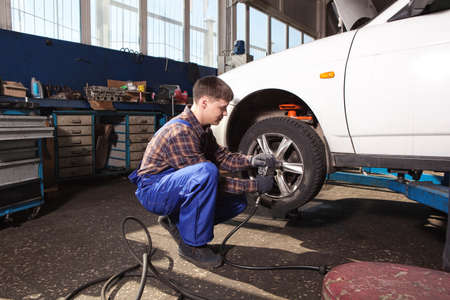 pneumatic tyres: Car mechanic screwing or unscrewing car wheel of lifted automobile by pneumatic wrench at repair service station Stock Photo