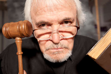 legally: Judge. Old male judge in a courtroom striking the gavel