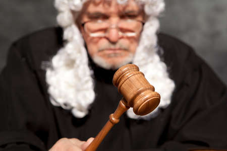 Judge. Old male judge in a courtroom striking the gavel