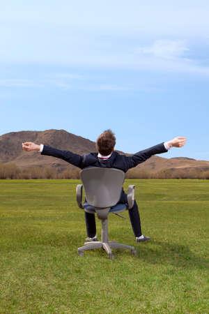 tilt views: Freelancer. Businessman sitting on chair on green meadow on blue sky background
