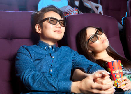 people watching: Young couple sitting at the cinema wearing 3d glasses, watching a film. Cinema photo series