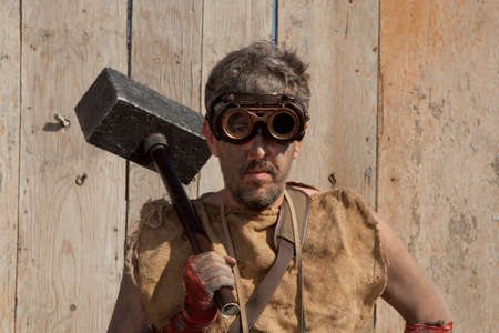 Steampunk man wearing glasses with sledge hammer Archivio Fotografico
