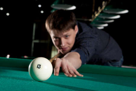 snooker rooms: Young man playing billiards in the dark billiard club Stock Photo