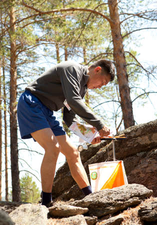 orienteering: RUSSIA, ULAN-UDE - MAY 22, 2016: Russian Azimut - 2016. Orienteering competition is held annually in the Buryatia region. People at at control point at orienteering course.