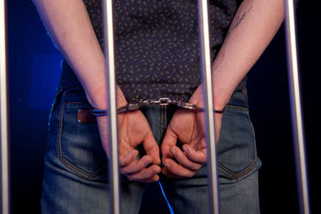 hands behind back: Arrested man in handcuffs with hands behind back