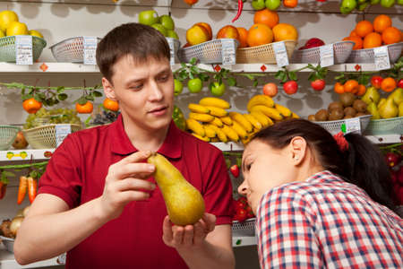 Assistant helping customer at vegetable counter of farm shop