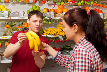 farm shop: Assistant helping customer at vegetable counter of farm shop Stock Photo