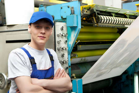 machine operator: Young man in cap working in newspaper factory