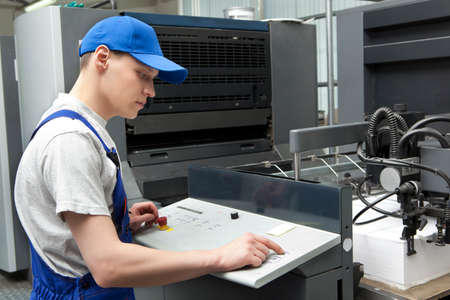 imprenta: Hombre joven en casquillo de trabajo en la fábrica de impresión Foto de archivo