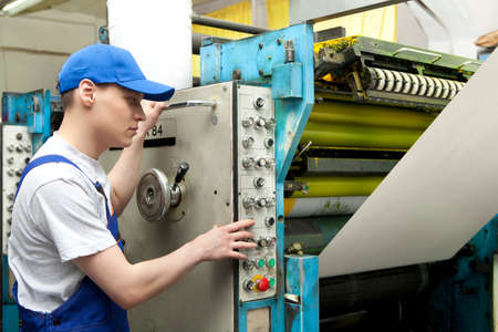 skilled operator: Young man in cap working in newspaper factory