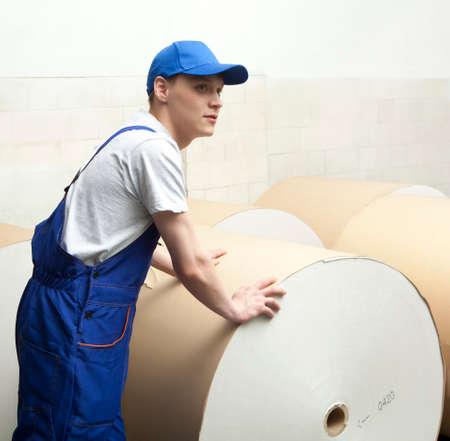 skilled operator: Man in cap pushing huge roll of paper in newspaper factory