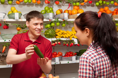 farm shop: Young woman buys cucumber. Assistant helping customer at vegetable counter of farm shop Stock Photo